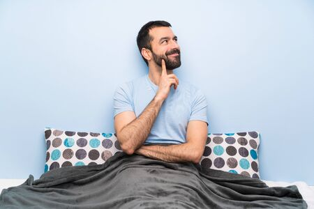 Man in bed thinking an idea while looking up Banco de Imagens