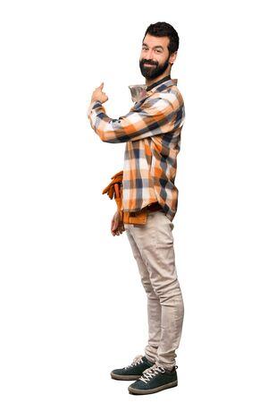 Uomo di artigiani che punta indietro su sfondo bianco isolato Archivio Fotografico