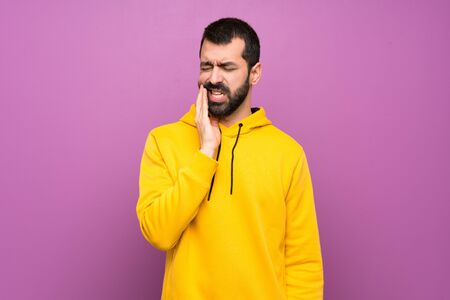 Handsome man with yellow sweatshirt with toothache Imagens