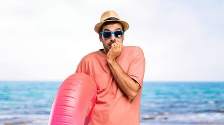 Man with hat and sunglasses on his summer vacation is a little bit nervous and scared putting hands to mouth at the beach