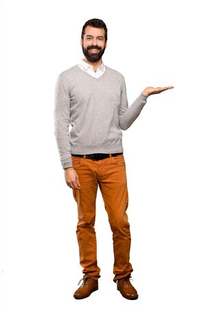 Handsome man holding copyspace imaginary on the palm to insert an ad over isolated white background Archivio Fotografico