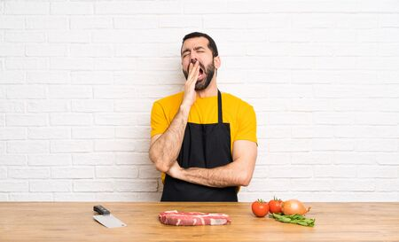 Chef holding in a cuisine yawning and covering wide open mouth with hand