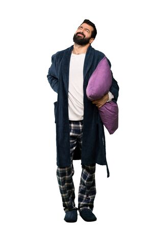 Man with beard in pajamas suffering from backache for having made an effort over isolated white background