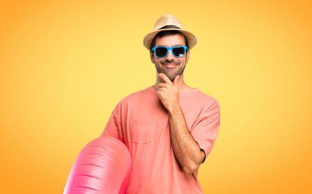 Man met hoed en zonnebril op zijn zomervakantie glimlachend en naar voren kijkend met zelfverzekerd gezicht op oranje achtergrond