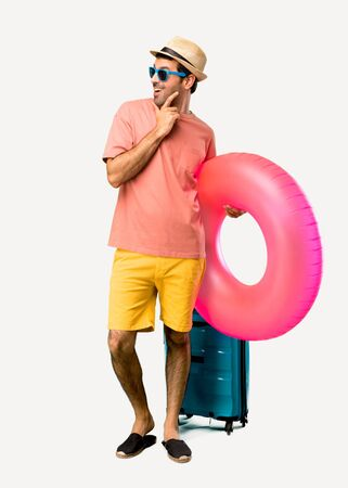 Full body of Man with hat and sunglasses on his summer vacation standing and looking to the side with the hand on the chin on isolated background
