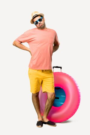 Full body of Man with hat and sunglasses on his summer vacation unhappy and suffering from backache for having made an effort on isolated background
