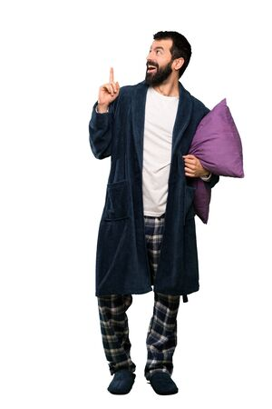 Man with beard in pajamas thinking an idea pointing the finger up over isolated white background