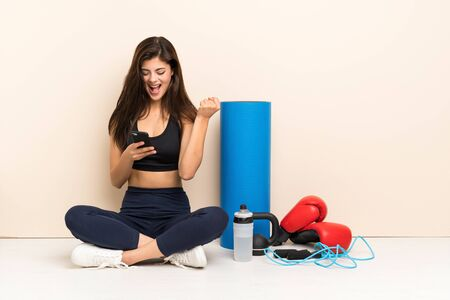 Teenager sport girl sitting on the floor with phone in victory position