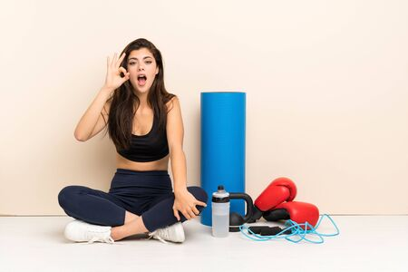 Teenager sport girl sitting on the floor surprised and showing ok sign