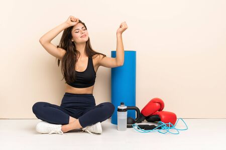 Teenager sport girl sitting on the floor celebrating a victory Stock Photo