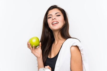 Teenager sport girl over isolated white background with an apple