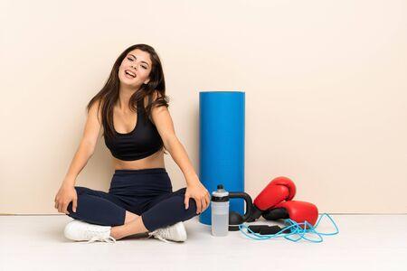 Teenager sport girl sitting on the floor smiling