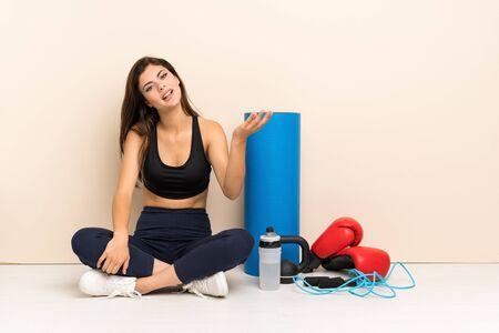 Teenager sport girl sitting on the floor making doubts gesture