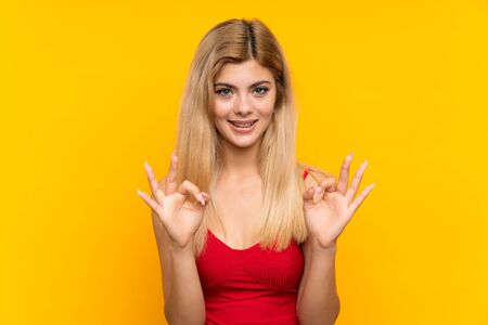 Teenager girl over isolated yellow background showing an ok sign with fingers