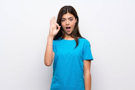 Teenager girl with blue shirt surprised and showing ok sign