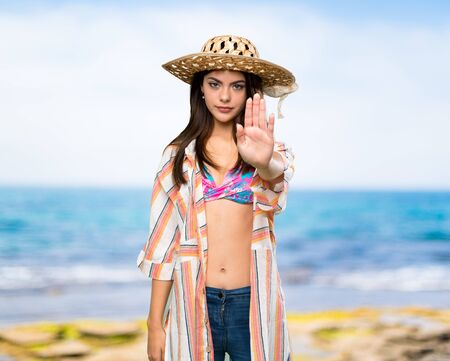 Teenager girl on summer vacation making stop gesture at the beach