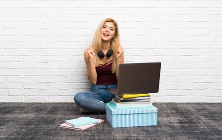 Teenager girl sitting on the floor with her laptop showing ok sign with fingers