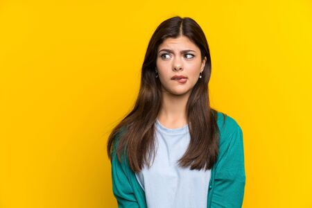 Teenager girl over yellow wall having doubts and with confuse face expression