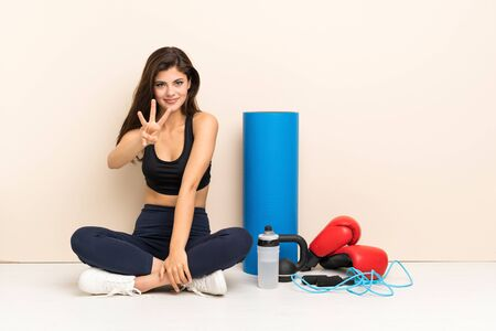 Teenager sport girl sitting on the floor happy and counting three with fingers