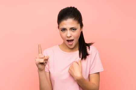 Teenager girl over isolated pink background with surprise facial expression 스톡 콘텐츠