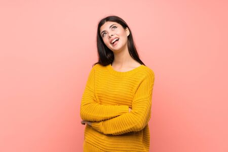 Teenager girl  over isolated pink wall looking up while smiling