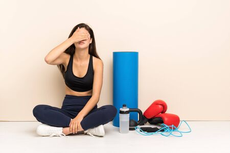 Teenager sport girl sitting on the floor covering eyes by hands. Do not want to see something