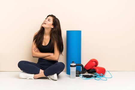 Teenager sport girl sitting on the floor happy and smiling