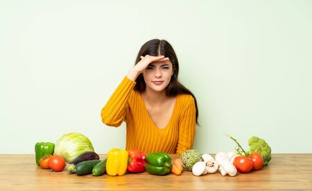 Teenager girl with many vegetables looking far away with hand to look something