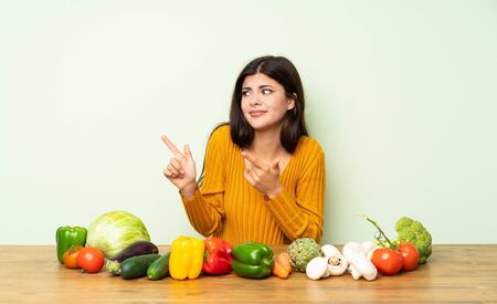 Teenager girl with many vegetables frightened and pointing to the side 版權商用圖片