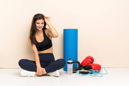 Teenager sport girl sitting on the floor with glasses and happy Stock Photo