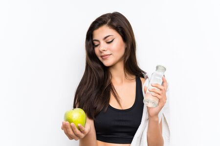Teenager sport girl over isolated white background with an apple and a bottle of water Stock Photo