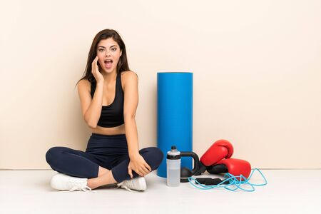 Teenager sport girl sitting on the floor with surprise and shocked facial expression Stock Photo