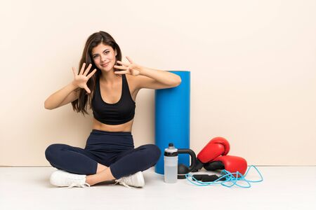 Teenager sport girl sitting on the floor counting nine with fingers Stock Photo