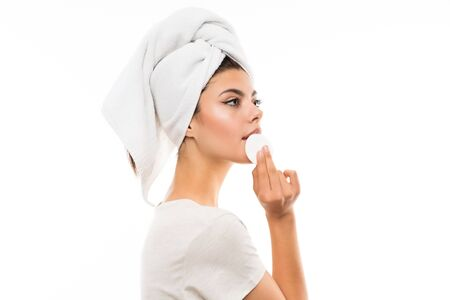 Teenager girl over isolated white backgroundremoving makeup from her face with cotton pad Reklamní fotografie