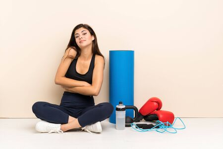 Teenager sport girl sitting on the floor making doubts gesture while lifting the shoulders