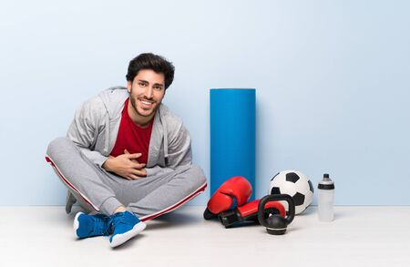 Sport man sitting on the floor smiling a lot Stock Photo