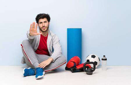 Sport man sitting on the floor making stop gesture