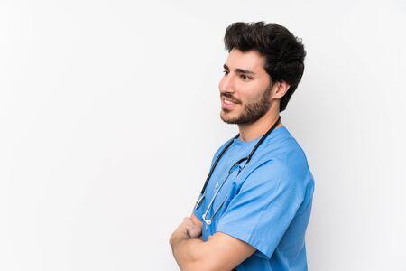 Chirurg dokter man over geïsoleerde witte muur staan en kijken naar de zijkant