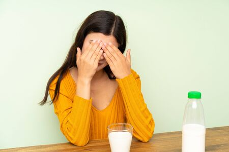 Teenager girl having breakfast milk covering her eyes Stock Photo
