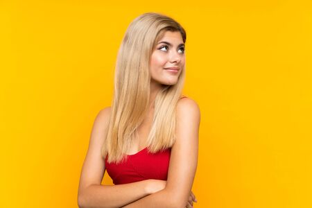 Teenager girl over isolated yellow background laughing