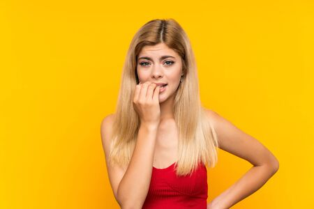 Teenager girl over isolated yellow background nervous and scared