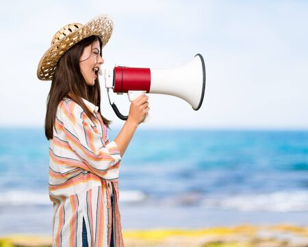 Teenager girl on summer vacation shouting through a megaphone at the beach 写真素材