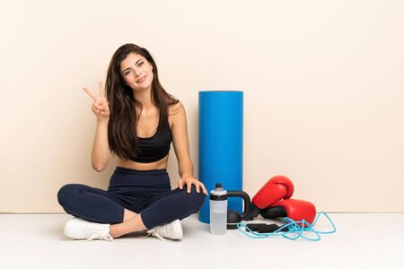 Teenager sport girl sitting on the floor smiling and showing victory sign