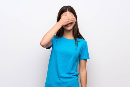Teenager girl with blue shirt covering eyes by hands. Do not want to see something