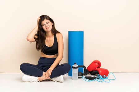 Teenager sport girl sitting on the floor with an expression of frustration and not understanding