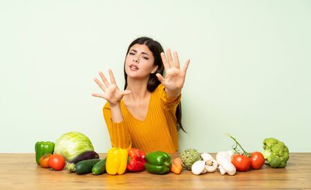 Teenager girl with many vegetables nervous stretching hands to the front Standard-Bild