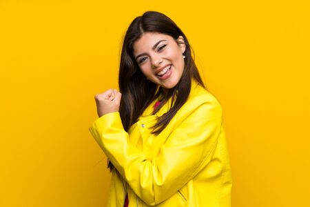 Teenager girl over yellow wall celebrating a victory