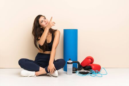 Teenager sport girl sitting on the floor pointing finger to the side