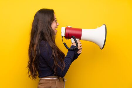 Teenager girl over isolated yellow wall shouting through a megaphone