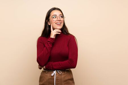 Teenager girl with glasses thinking an idea while looking up 免版税图像